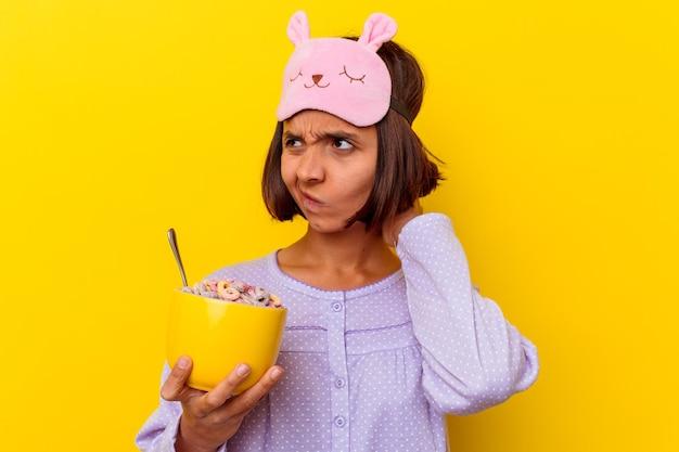 Junge frau der gemischten rasse, die müsli isst, die einen pijama tragen, der auf gelber wand lokalisiert wird, die hinterkopf berührt, denkt und eine wahl trifft.
