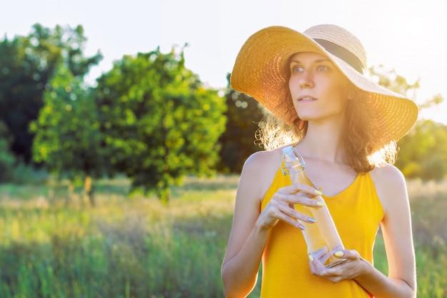 Junge frau der glücklichen schönheit mit reinem glas wasser trägt gelbes helles kleid und sommerhut lächelnd im freien im grünen park am sonnigen warmen lichttag. aktives outdoor-lifestyle-freizeitkonzept.
