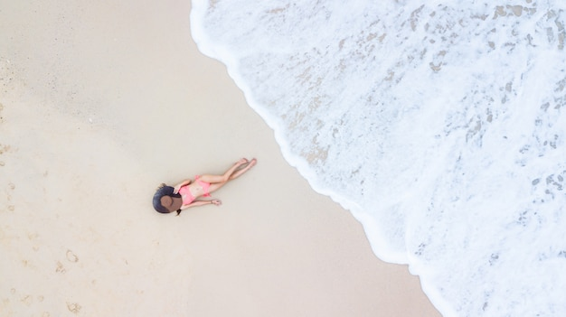 Junge frau der luftdraufsicht in einem bikini, der auf dem sand und den wellen liegt, junge frau, die auf dem weißen sandigen strand ein sonnenbad nimmt und sich entspannt