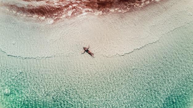 Junge frau der luftdraufsicht in einem bikini, der auf dem sandstrand und den wellen liegt