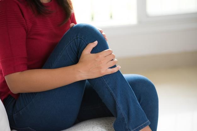 Junge frau der nahaufnahme, die auf sofa sitzt und knieschmerz fühlt