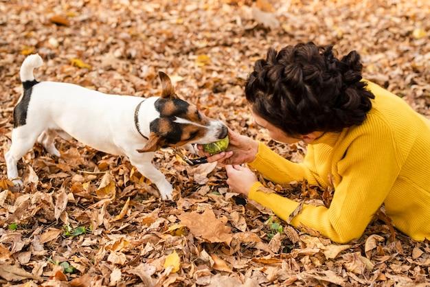 Junge frau der nahaufnahme, die mit ihrem hund spielt
