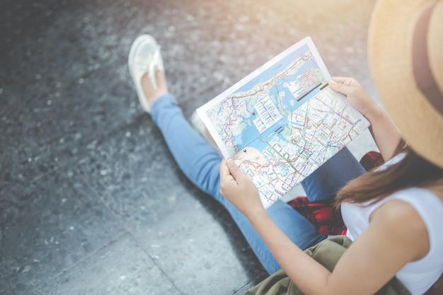 Junge frau der reisenden mit dem rucksack, der hält, halten eine karte an der bahnstation. tourismus tag.