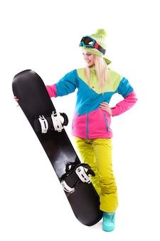 Junge frau der schönheit im skianzug und in den skibrillen halten snowboard