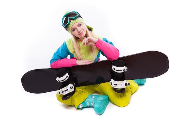 Junge frau der schönheit im skianzug und in den skigläsern sitzen mit sbowboard