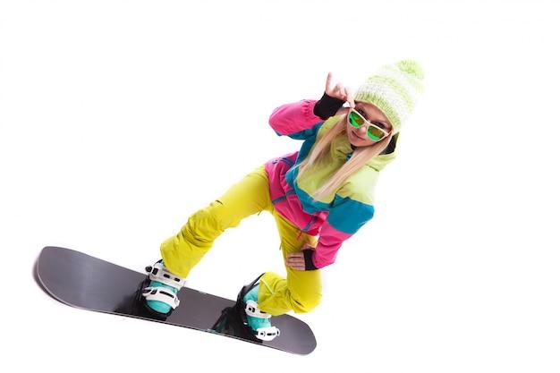 Junge frau der schönheit im skianzug und in der sonnenbrille reiten snowboard