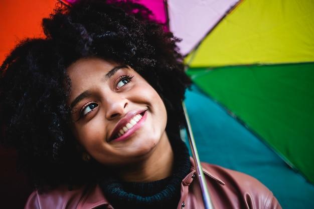 Junge frau der schwarzen ethnischen zugehörigkeit mit der regenbogenfarbenen flagge. schönes porträt des mädchens.
