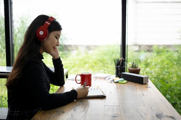 Junge frau der seitenansicht, die musik im kopfhörer hört und etwas auf notizbuch schreibt.