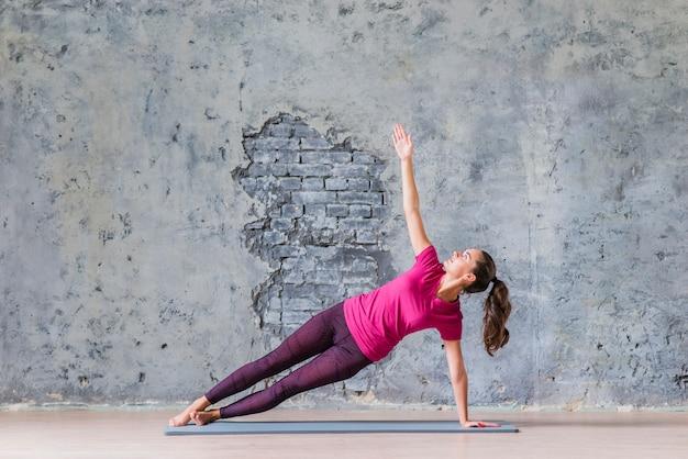 Junge frau der sportlichen eignung, die yogaübung tut