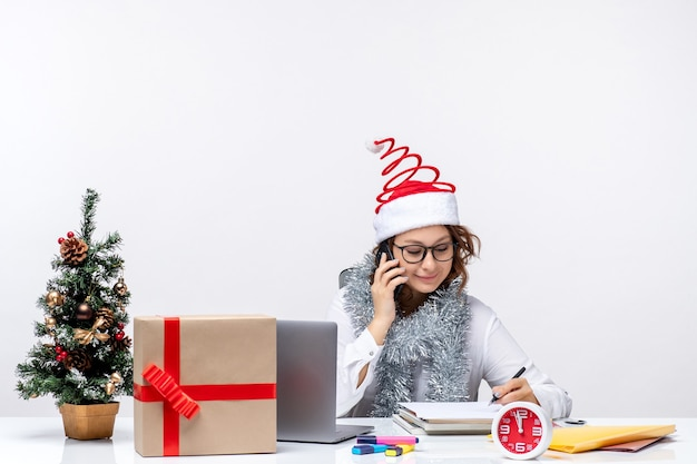 Junge frau der vorderansicht bei der arbeit während der feiertagstage, die am telefon auf weißem schreibtisch sprechen