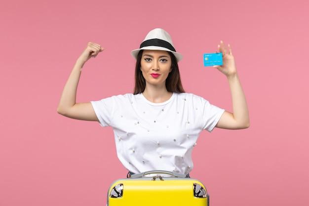 Junge frau der vorderansicht, die bankkarte auf der rosa wandfrauenreisesommeremotion hält