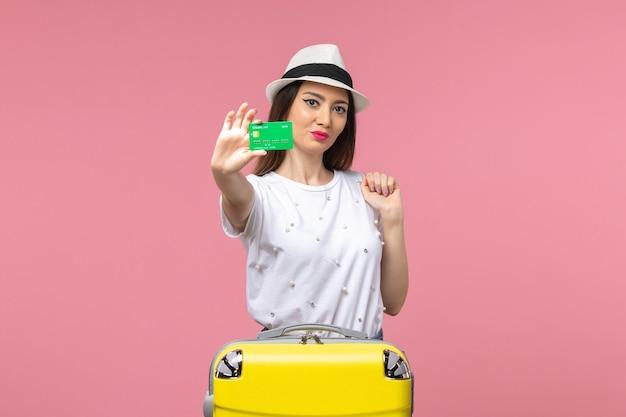 Junge frau der vorderansicht, die bankkarte auf der rosa wandgefühlsommerreisefrau hält