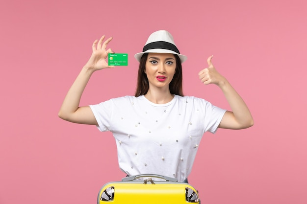 Junge frau der vorderansicht, die bankkarte auf der rosa wandsommerreisegefühlfrau hält