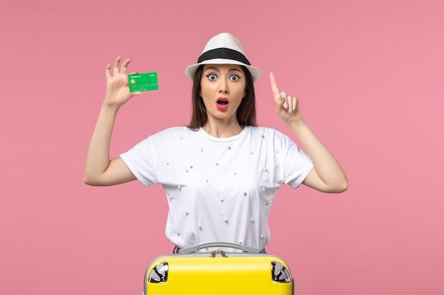 Junge frau der vorderansicht, die bankkarte auf rosa schreibtischgefühlsommerfrauenreise hält