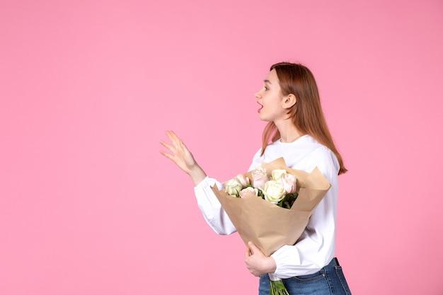 Junge frau der vorderansicht, die blumenstrauß von schönen rosen auf rosa hält