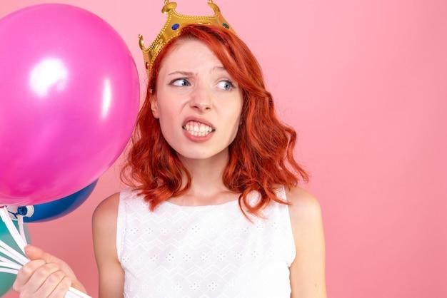 Junge frau der vorderansicht, die bunte luftballons auf dem rosa hält