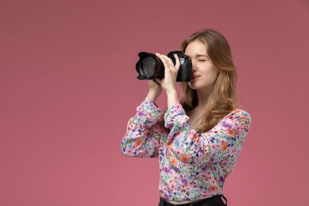 Junge frau der vorderansicht, die ein foto mit ihrer fotokamera macht