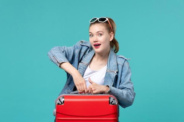Junge frau der vorderansicht, die für reise vorbereitet und auf blauem schreibtisch aufgeregt fühlt