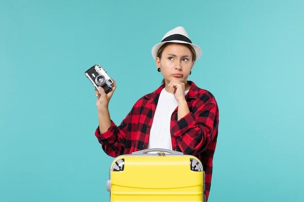 Junge frau der vorderansicht, die für urlaub vorbereitet und kamera auf blauem schreibtisch hält