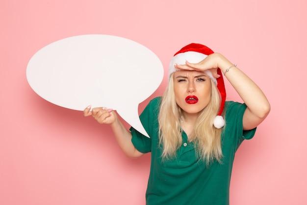 Junge frau der vorderansicht, die großes weißes zeichen hält, das auf einer rosa wandfoto-schneefarbe-neujahrsfeiertagsfrau schaut