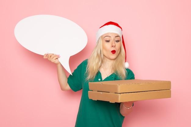 Junge frau der vorderansicht, die großes weißes zeichen und nahrungsmittelkästen auf rosa wandfotoarbeits-neujahrsferienjobkurier hält