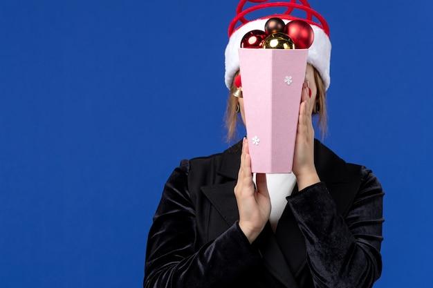 Junge frau der vorderansicht, die ihr gesicht mit spielzeugen auf neujahrsfeiertagen der blauen wandgefühle bedeckt