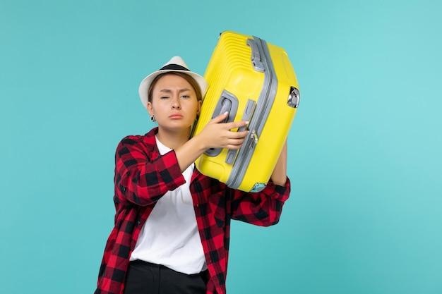 Junge frau der vorderansicht, die in den urlaub mit ihrer gelben tasche auf dem hellblauen raum geht