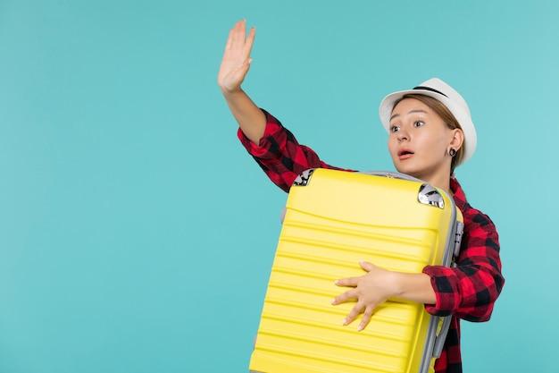 Junge frau der vorderansicht, die in den urlaub mit ihrer großen tasche geht, die auf blauem raum auf wiedersehen sagt