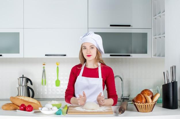 Junge frau der vorderansicht, die in der küche kocht