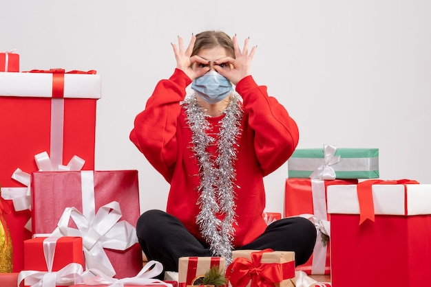 Junge frau der vorderansicht, die mit weihnachtsgeschenken in der sterilen maske sitzt
