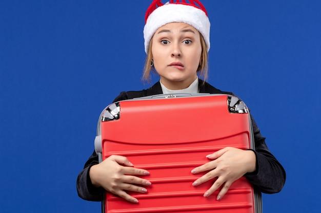 Junge frau der vorderansicht, die schwere rote tasche auf feiertagen der blauen wandferienfrau trägt