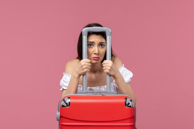 Junge frau der vorderansicht, die sich auf urlaub mit ihrer großen tasche vorbereitet, die auf rosa hintergrundreise, die ins ausland seereise reist, deprimiert fühlt
