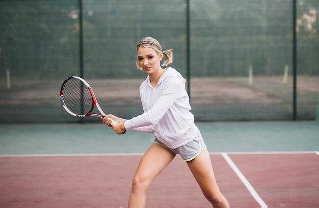 Junge frau der vorderansicht, die tennis spielt