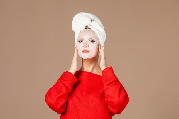 Junge frau der vorderansicht, die vorbereitet, gesichtsmaske auf rosa hintergrund anzuwenden