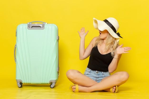 Junge frau der vorderansicht, die zusammen mit ihrer grünen tasche auf gelbem schreibtischreiseferiensonnenreise-reisemädchen sitzt