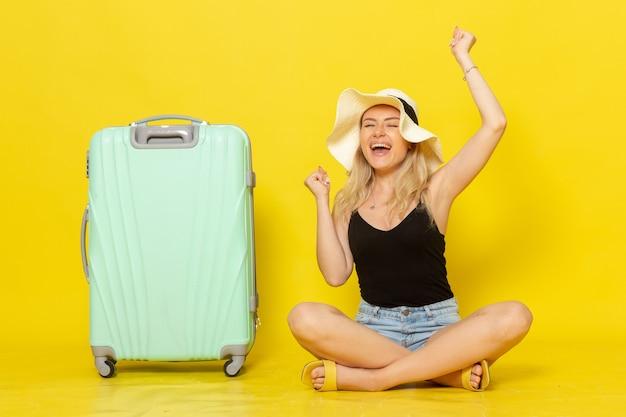 Junge frau der vorderansicht, die zusammen mit ihrer grünen tasche auf gelber wandreise-urlaubsreise-reisemädchen sitzt