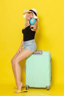 Junge frau der vorderansicht im urlaub, die auf ihrer grünen tasche hält globus auf der gelben wandfarbe weibliche reise reise meeressonne hält