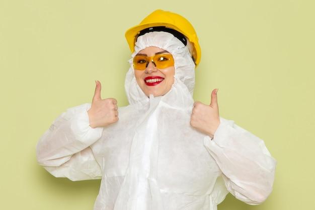 Junge frau der vorderansicht im weißen sonderanzug und im gelben helm lächelnd und zeigt wie zeichen auf dem grünflächenjob