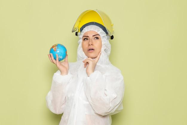 Junge frau der vorderansicht im weißen sonderanzug und im gelben schutzhelm, der kleinen globus hält, der auf der grünfläche denkt