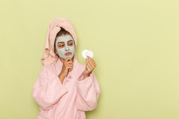 Junge frau der vorderansicht nach der dusche im rosa bademantel, der baumwollrunden auf grüner oberfläche hält