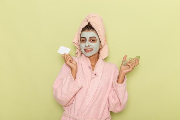 Junge frau der vorderansicht nach der dusche im rosa bademantel, der sprays und karte auf grünem schreibtisch hält