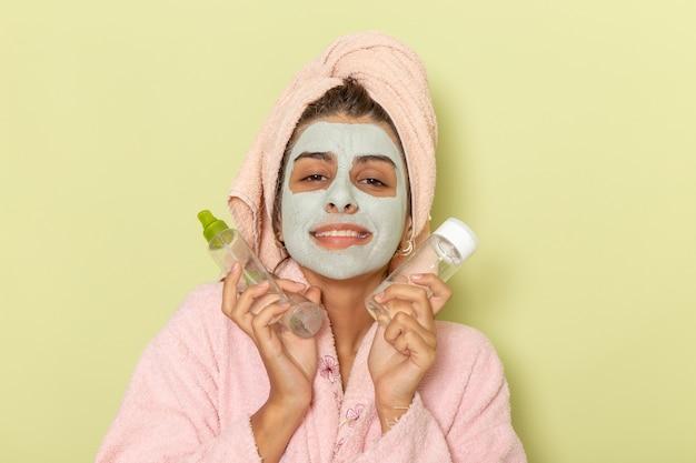 Junge frau der vorderansicht nach dusche im rosa bademantel, der make-up-entferner auf grüner oberfläche hält