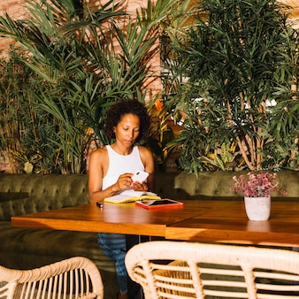 Junge frau des afroamerikaners, der intelligentes telefon im luxusrestaurant verwendet