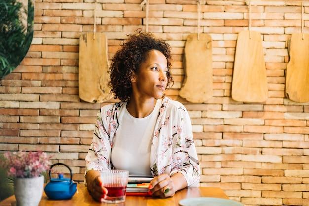 Junge frau des afroamerikaners, die im restaurant mit cocktail auf holztisch sitzt