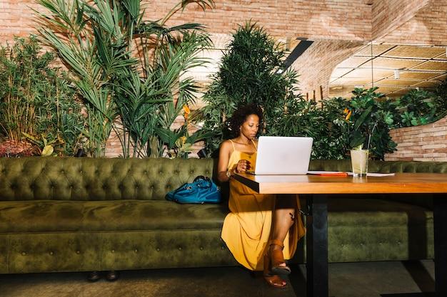 Junge frau des afroamerikaners, die im restaurant unter verwendung des laptops sitzt