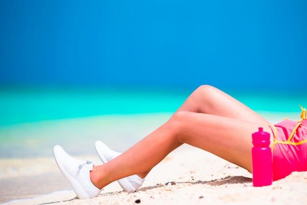 Junge frau des aktiven sitzes in ihrer sportkleidung während der strandferien