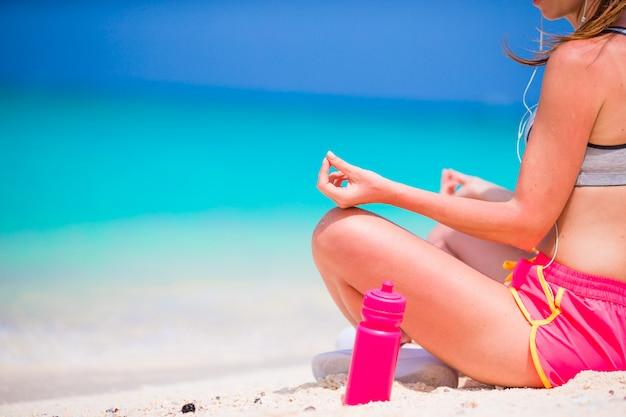 Junge frau des aktiven sitzes in yogaposition an ihrer sportkleidung während der strandferien