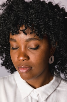 Junge frau des attraktiven afroamerikaners mit geschlossenen augen
