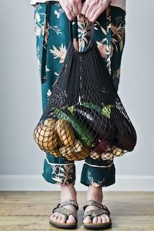 Junge frau des einkaufskonzeptes, die textileinkaufstüte mit abfallfreien plastikkartoffeln des gemüses null hält