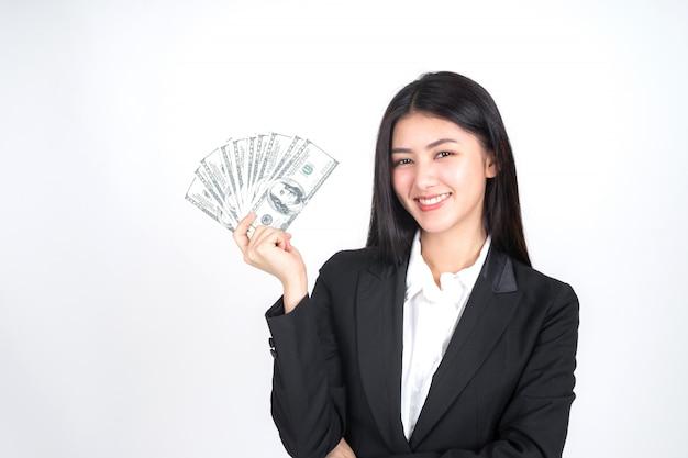 Junge frau des erfolgreichen schönen asiatischen geschäfts, die in der hand geld us-dollar rechnungen hält